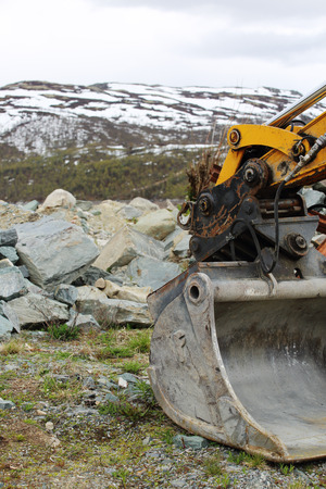 Excavator bucket moving stones in mountains close-up