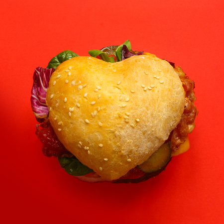 Heart shaped hamburger, love burger fast food concept, on red background, top view