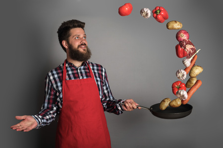 Cooking man concept, smiling bearded man in checked shirt, drop up meat and vegetables from a pan, studio shot on gray background