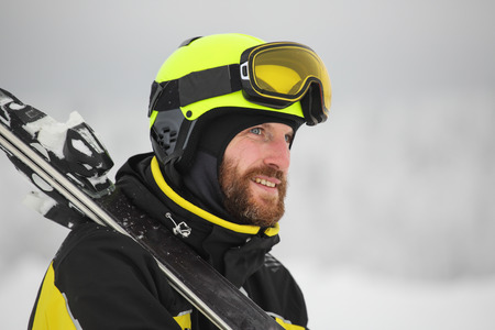 Portrait of a happy male skier in the alps with ski on shoulder