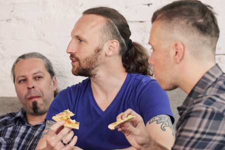 Group of men drinking beer, eating pizza, talking and smiling while resting at home on couch behind TV