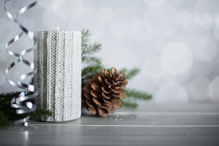 Silver Christmas new year candle with curly streamer ribbon bow decoration over glittering bokeh lights background with copy space for text 스톡 콘텐츠