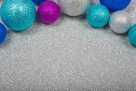 Christmas decoration of colorful glitter balls on silver glitter background with copy space for text new year card concept