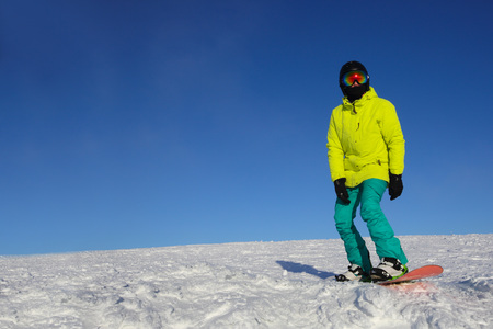 Snowboarder riding on slope at ski resort at sunny day