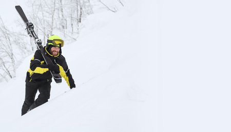 Happy smiling skier walks in the mountains in deep snow after freeride alpine skiing with ski on shoulder