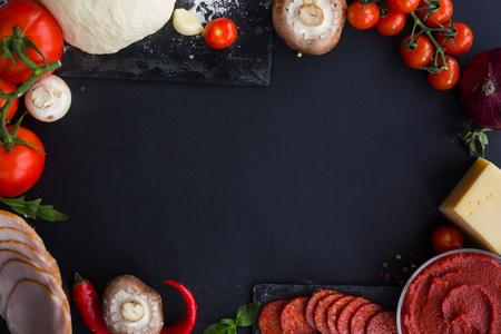 Masa cruda para pizza con ingredientes y especias en el marco del borde del fondo de la tabla negra con espacio para copiar texto