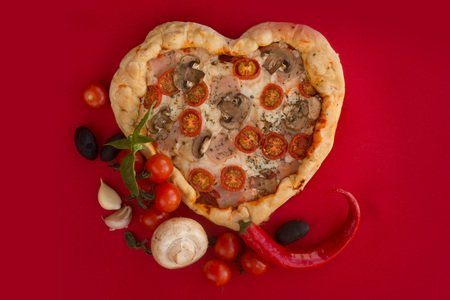 Pizza heart shaped with ham tomatoes and mushrooms on red background . Concept of romantic love for Valentines Day . Love food