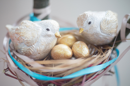 Two cute handmade small birds and their golden eggs in nest , parentind, care, easter concept Stockfoto