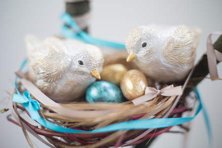 Two cute handmade small easter birds and their golden eggs in nest , parenting , adoption , care concept
