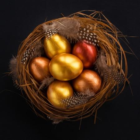 Joyeuses fêtes de Pâques symbole de voeux nid d'herbe en bois naturel élégant avec des œufs de caille dorés sur fond noir