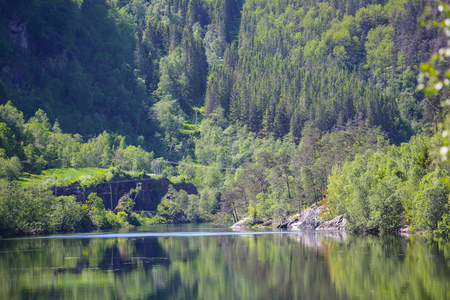 Beautiful spring landscape with silent lake, forest and mountains in Stolsheimen area, Norway Фото со стока