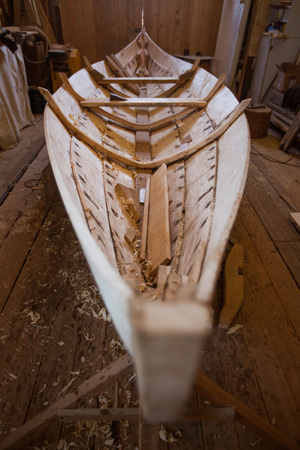 Handmade wooden boat in the barn close up view