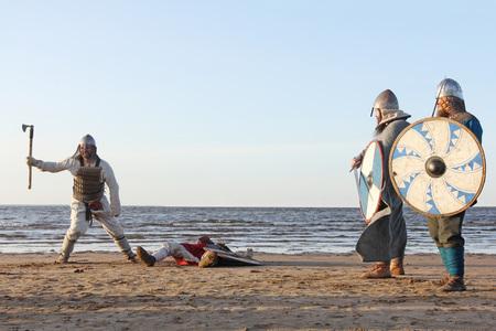 Dos guerreros eslavos medievales luchan con espadas y escudos en la playa