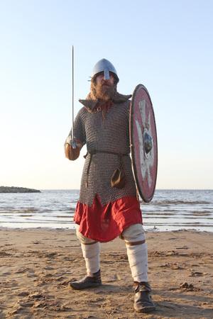 Portrait of slavic warrior reenactor with sword and shield posing outdoors at seaside 版權商用圖片
