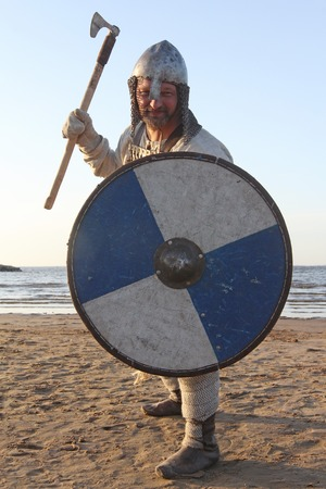 Portrait of slavic warrior reenactor with sword and shield posing outdoors at seaside 免版税图像