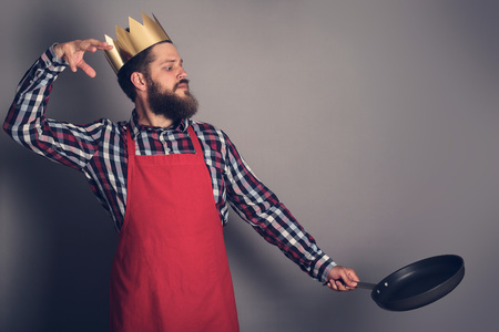 Cooking man concept, king of kitchen,bearded man in checked shirt, drop up something from a pan, studio shot on gray background copy space for text