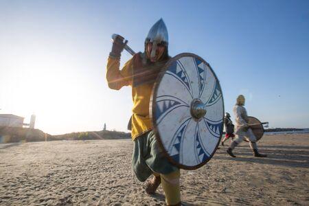 Reenactor guerrero eslavo con entrenamiento de hacha y escudo al aire libre en la playa, corriendo a la cámara