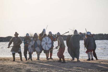 Slavic warriors reenactors with wearpons and shields training fighting outdoors at seaside Stockfoto