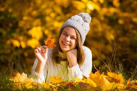Portrait of pretty nice teenage girl with dental braces in autumn park , background with copy space for text