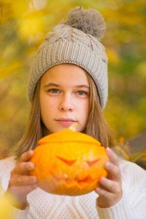 Teenage girl holding halloween pumpkin over orange autumn park background