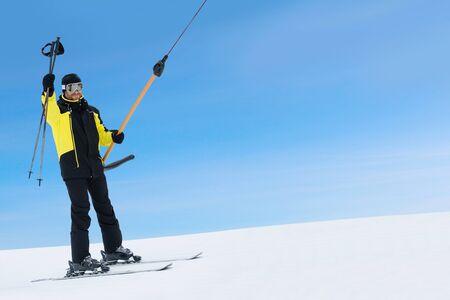 Happy smiling male skier using t bar ski drag lift and greeting waving his ski poles