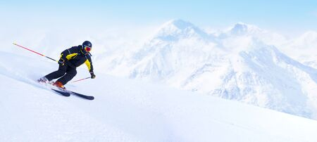 Alpine skier in high mountains skiing downhill on piste copy space for text , sli slope, ski resort, alpine skiing