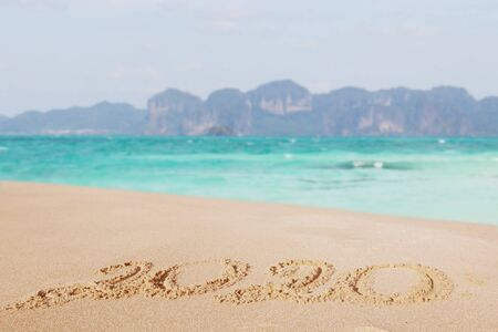 Happy New Year 2020, lettering on the beach. Numbers 2020 year on the sea shore, message handwritten in the golden sand on beautiful beach background. New Years concept. Stock Photo