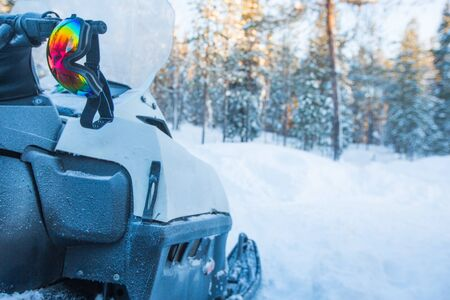 Snowmobile in winter snow forest in the morning side view and protective mask goggles glasses ready for adventure