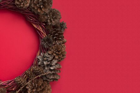 Christmas natural eco style spruce pine cone wreath over red background flat lay top view with copy space for text Stock fotó