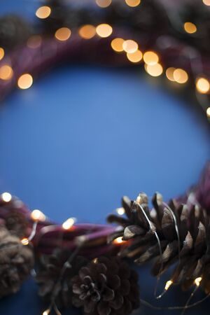 Christmas wreath of pine cones and glowing lights garland on blue background copy space text