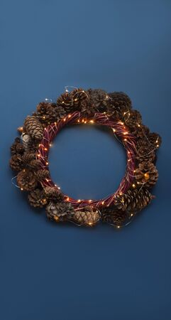 Christmas wreath of pine cones and glowing lights garland on blue background top view flat lay copy space text Stock fotó