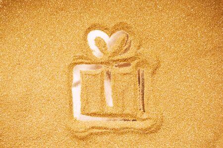 Hand drawn Christmas gift box symbol on golden glitter background