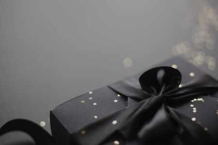 Black friday gift, paper box with silk ribbon bow on black paper background with copy space for text Stockfoto