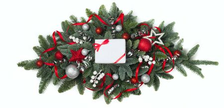 Christmas design element of noble fir tree branches and red baubles isolated on white background