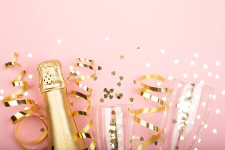 Valentines day champagne bottle flute glasses golden confetti hearts and serpentine on pink background with copy space for text Stockfoto