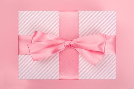 Valentines Day gift in a box wrapped in striped paper and tied with silk ribbon bow on pink background with copy space for text Фото со стока