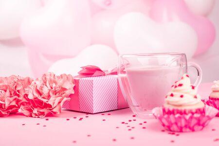 Valentinstaggeschenk in einer Schachtel, die in gestreiftes Papier eingewickelt und mit Seidenbandschleife und Dessert auf rosa Ballonhintergrund mit Kopierraum für Text gebunden ist