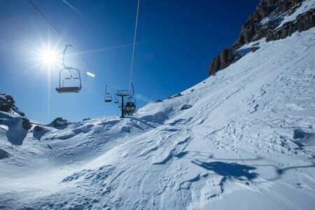 Ski lift chairs on bright winter day Dolomities Dolomiti Italy in wintertime beautiful alps mountains and ski slope Cortina d'Ampezzo Cinque torri mountain peaks famous landscape skiing resort area Banco de Imagens