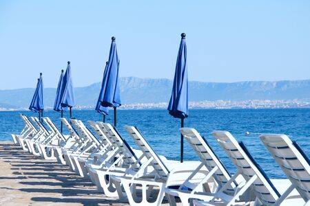 Rows of empty chaise-lounges over sea background, Supetar, Brac island, Croatia