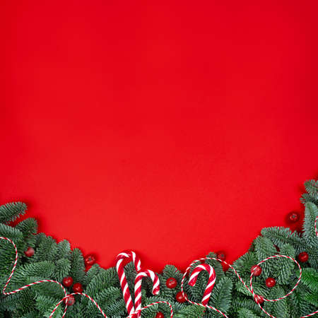 Christmas fir tree branches and baubles decor border frame on red background with copy space for text Stock Photo