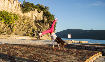 acrobatics: Girl is engaged in acrobatics on the beach.