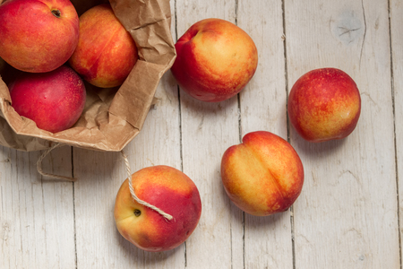 Nectarines in kraft bag on a wooden background. Healthy eating