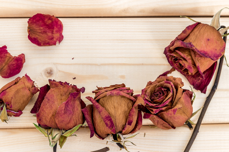 dried flower arrangement: A bouquet of dried flowers on a wooden background. Postcard, background with place for inscription. Dry roses as a decoration.