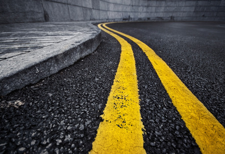 Detail of curved double yellow line on black asphalt painted along curb Stockfoto