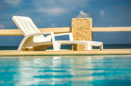 Empty white plastic sunbed next to pool Stock Photo