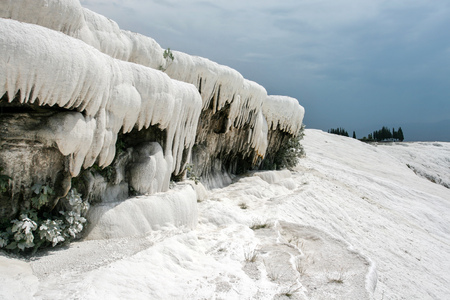 White travertine forming icicles / stalactites like objects, making landscape looks as snow covered winter scenery even tough it is hot summer day. Pamukkale (Cotton Castle), Hierapolis, Turkey.