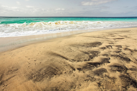 Gorgeous empty beach with golden and black volcanic spots sand, with azure sea in the background. Sal, Cape Verde Stock Photo