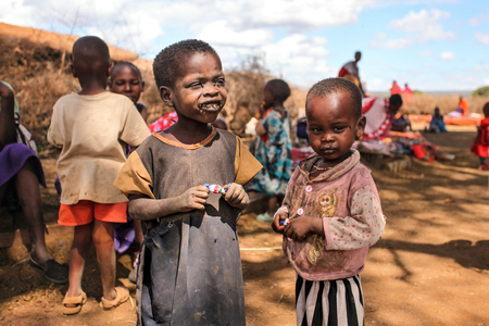 Unknown Masai village near Amboselli park, Kenya - April 02, 2015: Poor dirty Masai children with faces and mouth covered with flies.