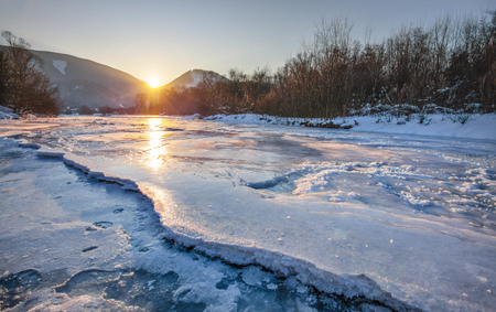 River Bela completely frozen during extreme cold, early morning sun rising behind mountains reflected in ice layer with snow patches. Liptovsky Hradok, Slovakia