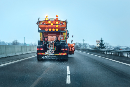 View from the car behind orange highway maintenance truck spreading de-icing salt and sand, crystals dropping on the ice covered asphalt road. Stock Photo